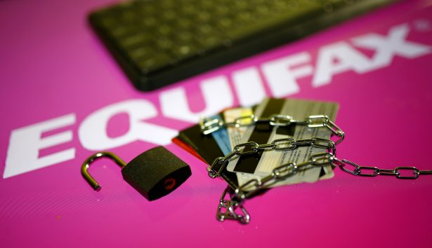 Credit cards, a chain and an open padlock is seen in front of displayed Equifax logo