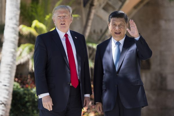 Chinese President Xi Jinping (R) waves to the press as he walks with US President Donald Trump