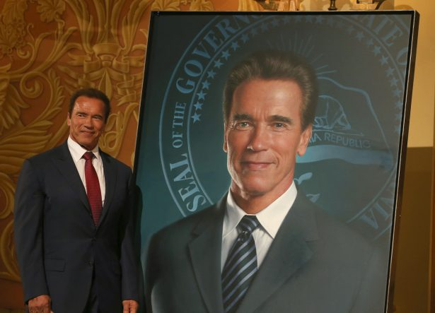 Former California Gov. Arnold Schwarzenegger poses next to his gubernatorial portrait