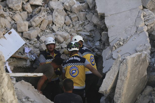 Syrian White Helmet civil defense workers search for victims