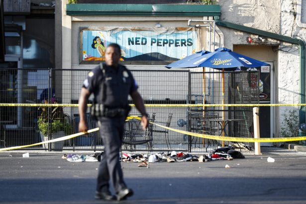 Policeman walk by shoe pile outside the scene of a mass shooting in Ohio