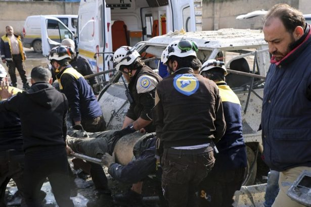 The members of the Syrian Civil Defense transporting an injured person after an airstrike hit the northern town of Maaret