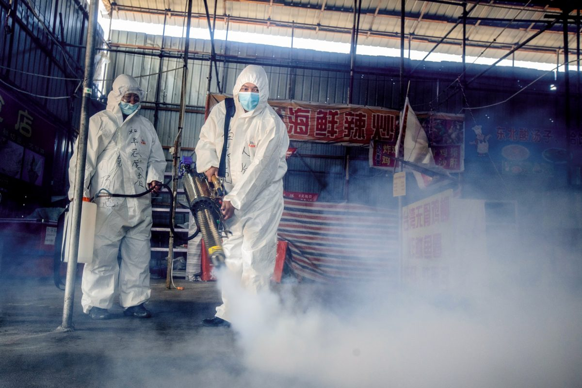 Two volunteers are spraying disinfectant at a market in the border city of Suifenhe