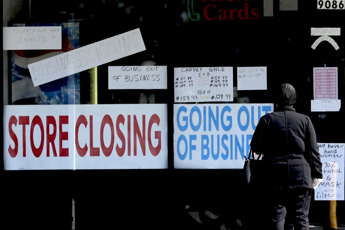 A woman looks at signs at a store closed