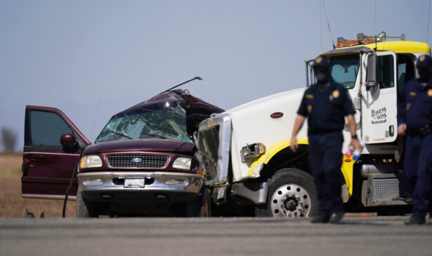 Law enforcement officers work at the scene of a deadly crash