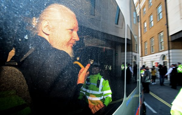 Julian Assange gestures to the media from a police vehicle on his arrival at Westminster Magistrates court in London, England