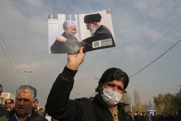 A man holds a picture of Iran's supreme leader Ayatollah Ali Khamenei
