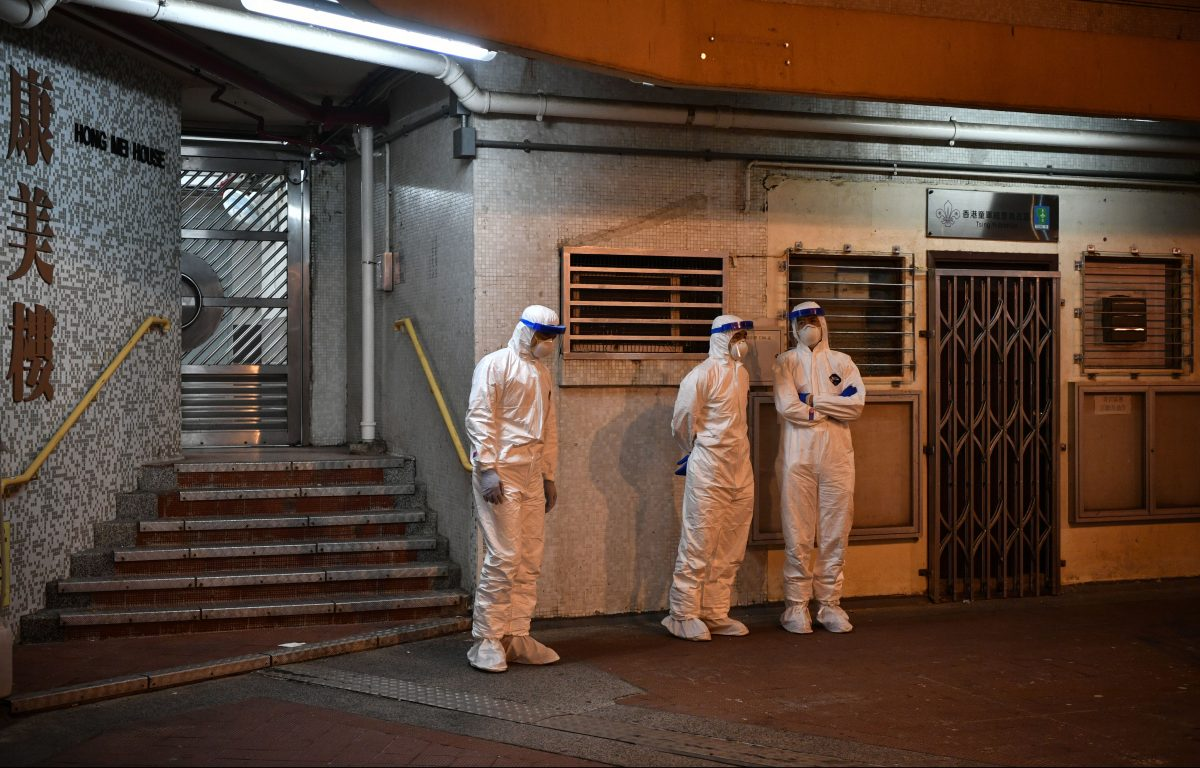 Medical personnel stand outside a block